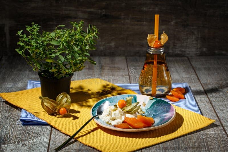 Una composición brillante de una placa redonda, de una botella anaranjada, y de un árbol chino verde Un sistema de cena lindo en  fotos de archivo