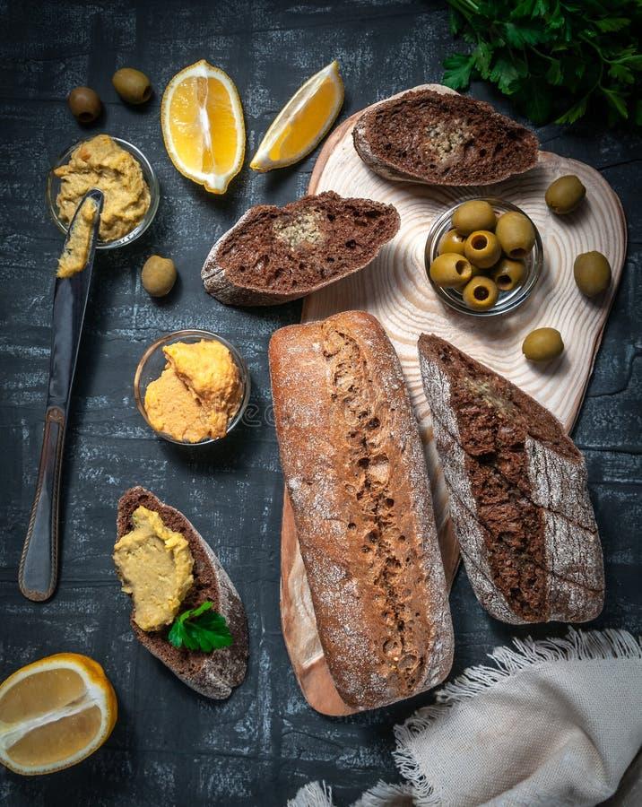Una composición de dos baguettes de salvado y de harina entera del grano Bocadillo del hummus y de aceitunas En el espaciamiento  foto de archivo libre de regalías
