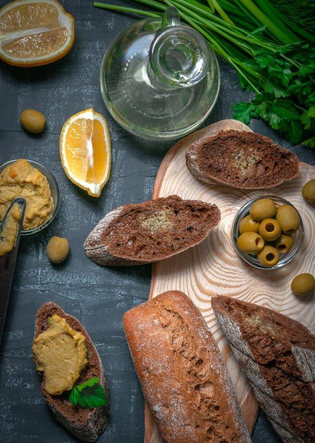 Una composición de dos baguettes de salvado y de harina entera del grano Bocadillo del hummus y de aceitunas Un buque con el acei fotografía de archivo