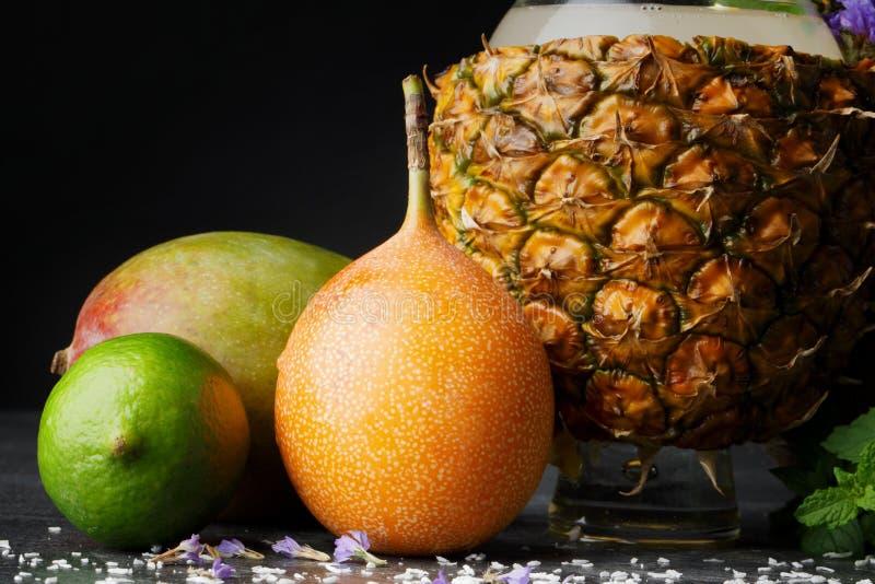 Una composizione dei frutti di estate Agrumi variopinti e una tazza dell'ananas Mango, calce e pompelmo su un fondo nero fotografia stock libera da diritti
