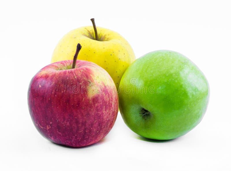 Una composizione di tre mele sulla natura morta verde, gialla e rosso- di un fondo bianco - immagini stock