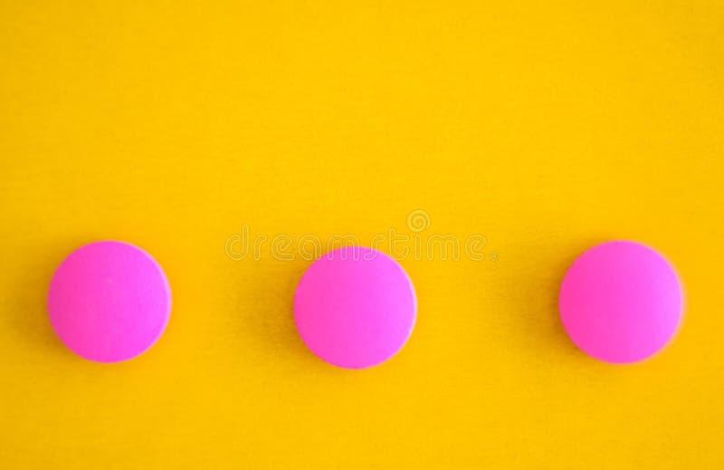 Una composizione di tre pillole rotonde rosa su un fondo giallo Disposizione piana Copi lo spazio Primo piano di tendenza fotografia stock