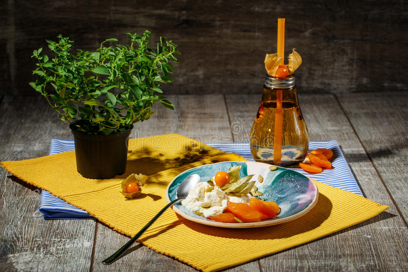Una composizione luminosa di un piatto rotondo, di una bottiglia arancio e di un albero cinese verde Un insieme di cena sveglio s fotografia stock