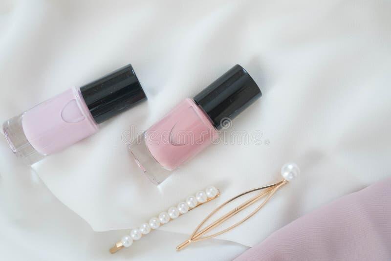 Una composizione piana di smalto e delle forcelle femminili dorate decorati con le perle Primavera o estate di modo e moderna immagine stock libera da diritti
