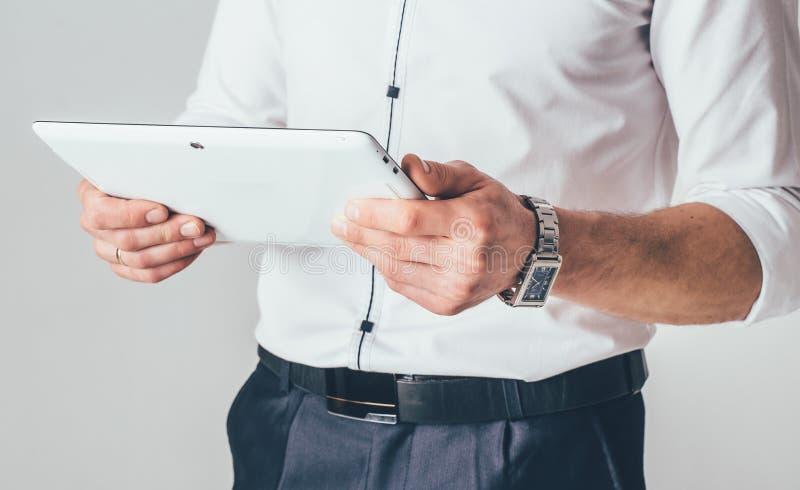 Una compressa bianca è nelle mani di un uomo Sta in una camicia bianca e nei pantaloni neri e legge le informazioni dall'aggeggio fotografia stock