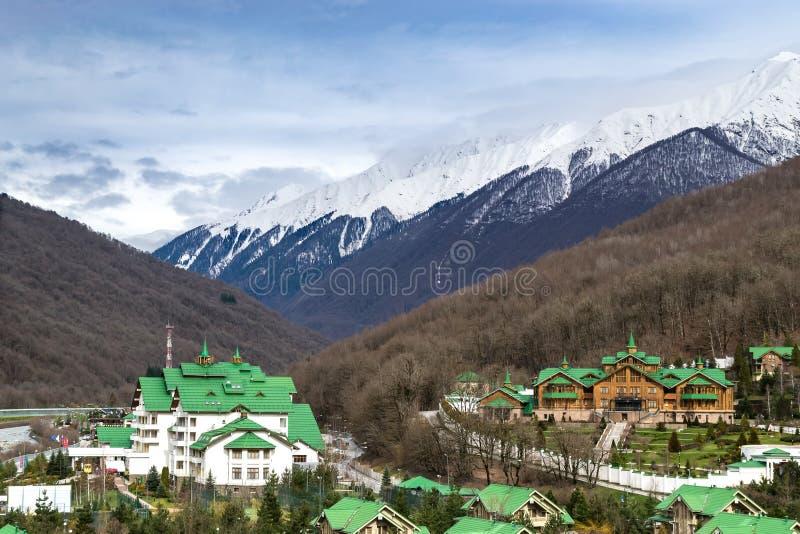 Una comunidad moderna de la cabaña con una casa con los tejados verdes situados entre las montañas fotos de archivo