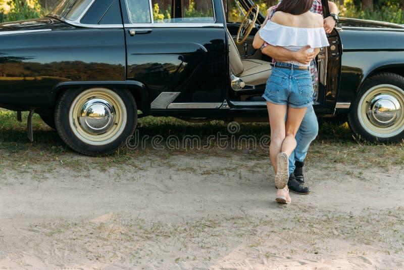 Una condizione delle coppie abbraccia contro il contesto di un'automobile nera, un uomo che si appoggia la porta di automobile Fo immagine stock