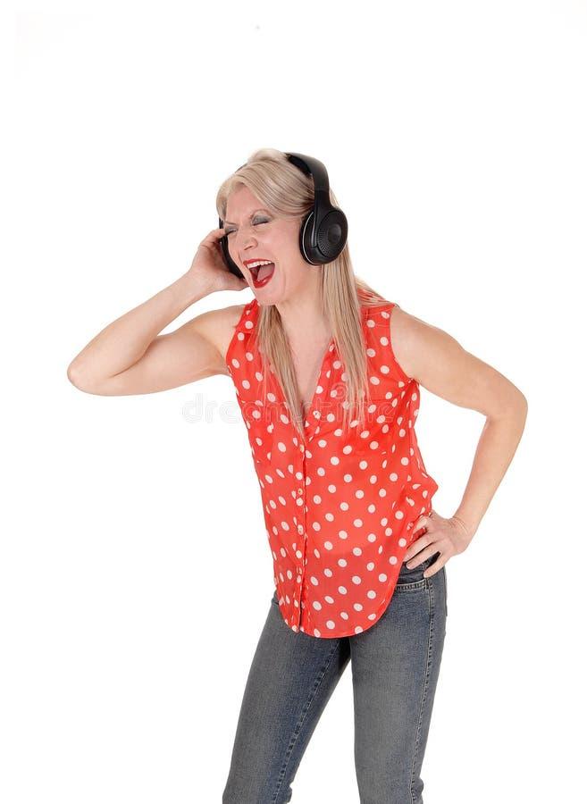 Una condizione esile della donna in jeans e cantare fotografie stock libere da diritti