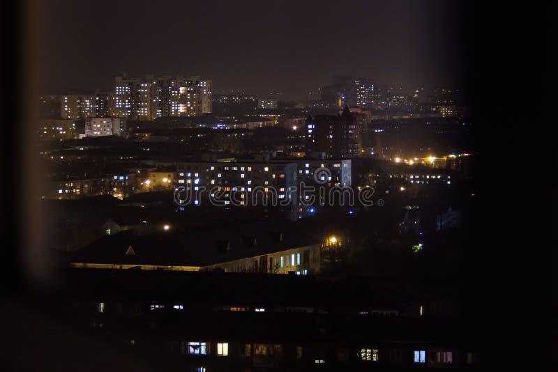 Una construcción de viviendas en la noche Ventanas residenciales de los planos que se encienden para arriba y que apagan durante  fotografía de archivo