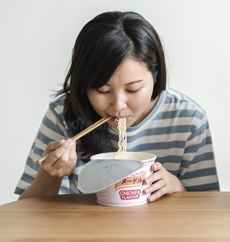 Una consumición asiática joven de la mujer tallarines inmediatos fotografía de archivo