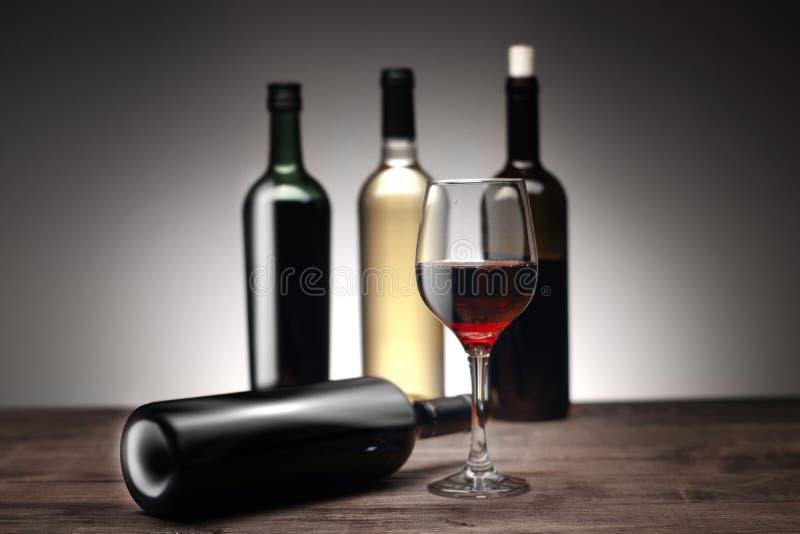 Una copa de vino con las botellas foto de archivo