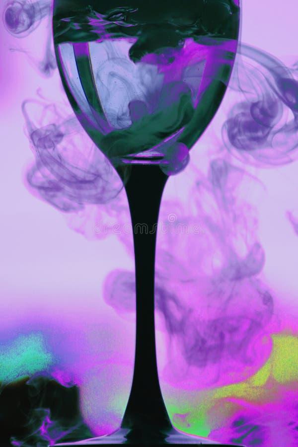 Una copa de vino en una pierna negra y pares brillantes de diversos colores alrededor Abstracci?n fotografía de archivo