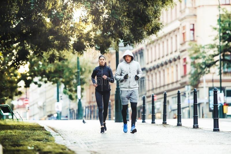 Una coppia adatta che corre all'aperto sulle vie della città di Praga fotografia stock