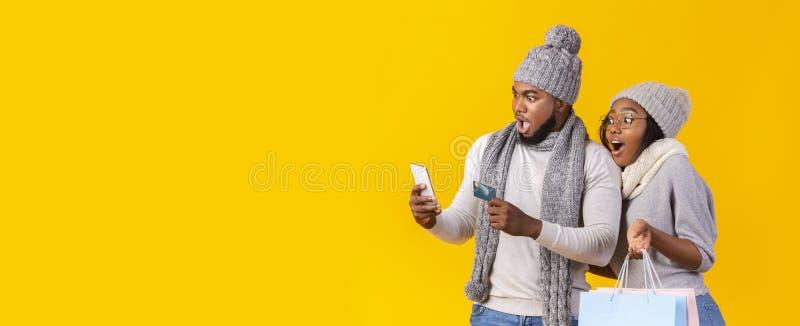 Una coppia africana sbalorditiva che fa shopping al telefono, online banking immagini stock libere da diritti
