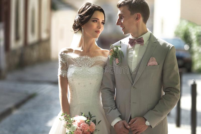 Una coppia amorosa delle persone appena sposate cammina nella città e nel sorriso La sposa in un bello vestito, lo sposo si è ves immagini stock libere da diritti