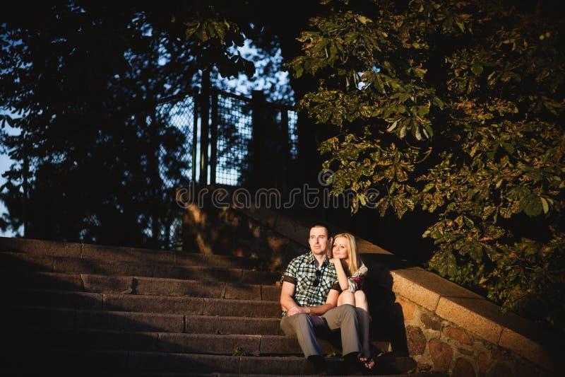 Una coppia amorosa sta sedendosi sui punti immagini stock