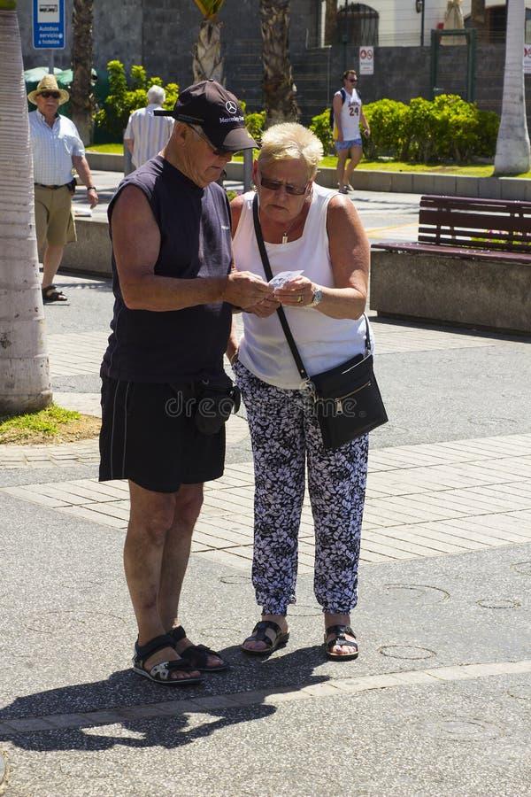 Una coppia anziana controlla la a fino alla ricevuta sulla via principale di Playa Las Americhe in Tenerife immagini stock