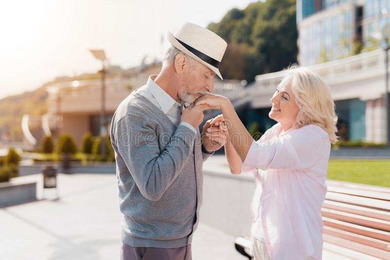 Una coppia anziana sta camminando nel quadrato L'uomo bacia la mano del ` s della donna La parte posteriore può vedere il mare ed fotografia stock libera da diritti