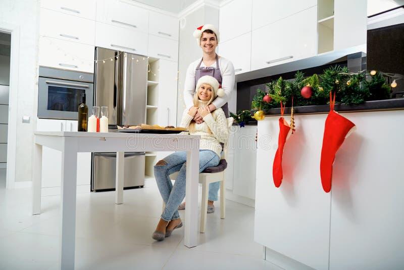 Una coppia in cappelli di Santa Claus ad una tavola nella cucina su Cristo fotografia stock libera da diritti
