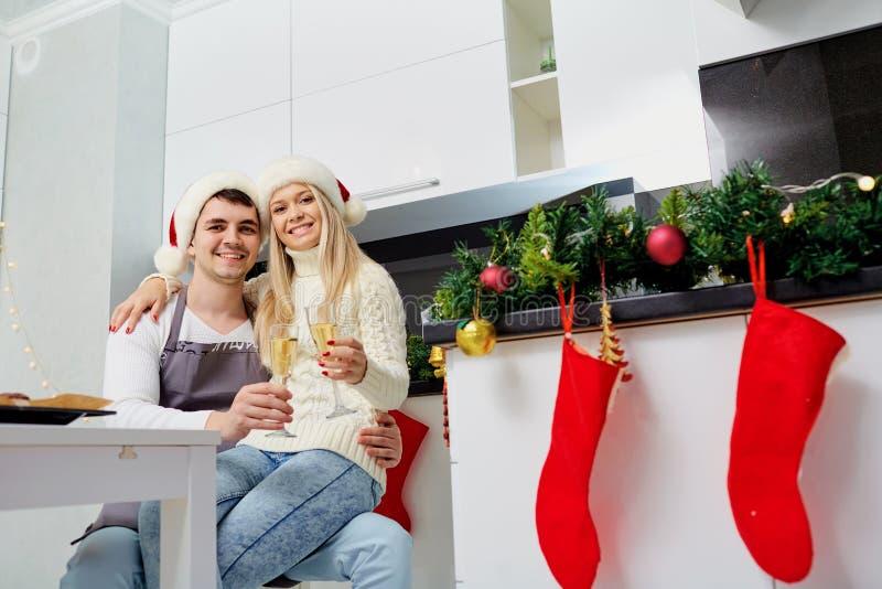 Una coppia in cappelli di Santa Claus con i vetri del champagne sul Natale immagini stock