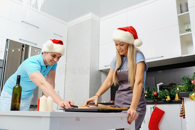 Una coppia in cappelli di Santa Claus cuoce i bigné sul Natale in K fotografia stock