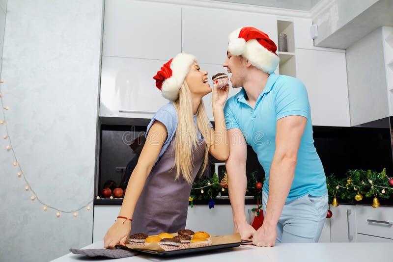 Una coppia in cappelli di Santa Claus cuoce i bigné sul Natale in K immagini stock