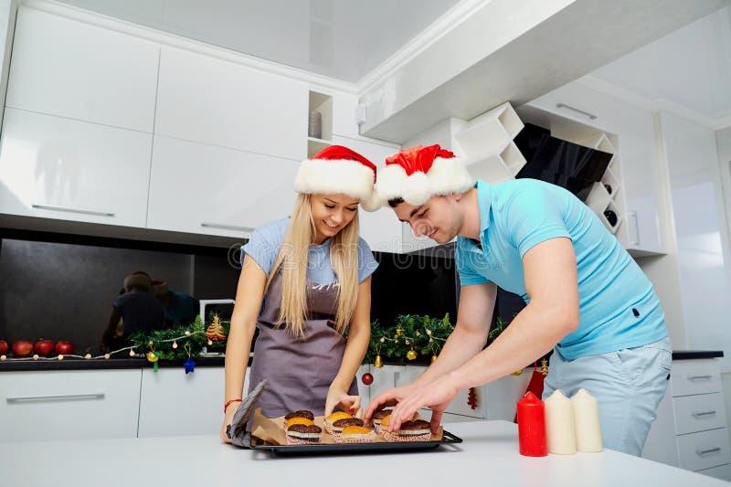 Una coppia in cappelli di Santa Claus cuoce i bigné sul Natale in K fotografia stock libera da diritti
