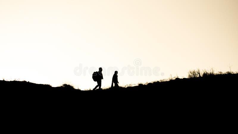 Una coppia che cammina al tramonto su una collina fotografie stock libere da diritti
