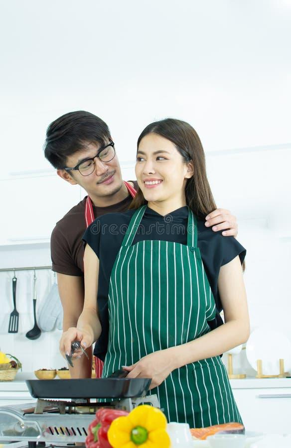 Una coppia che cucina per la cena nella cucina fotografia stock libera da diritti