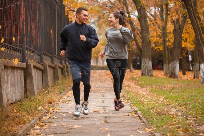 Una coppia che gioca gli sport che corrono nel parco di autunno all'aperto fotografia stock libera da diritti