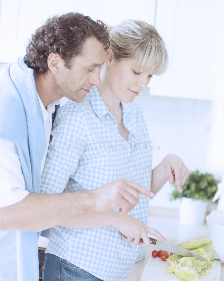 Una coppia che produce un'insalata sana nella cucina fotografia stock libera da diritti