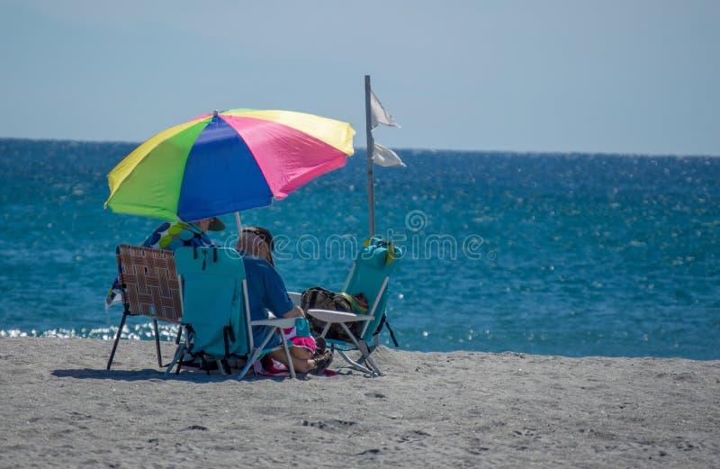 Una coppia che si siede sotto un ombrello sulla sabbia su una spiaggia in Florida immagine stock