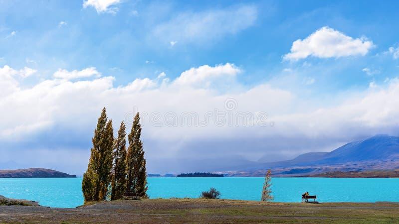 Una coppia che si siede su un banco nel lago Tekapo fotografie stock