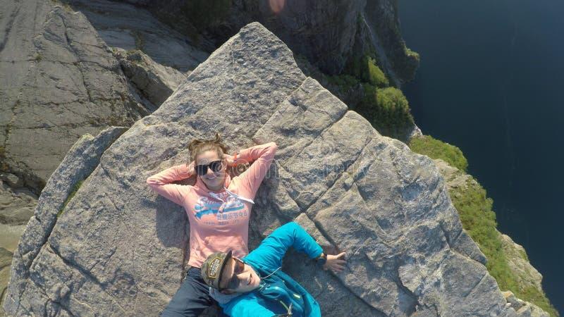 Una coppia che si trova sull'orlo della roccia famosa di Preikestolen in Norvegia Un tramonto sta avendo luogo sopra un fiordo fotografia stock