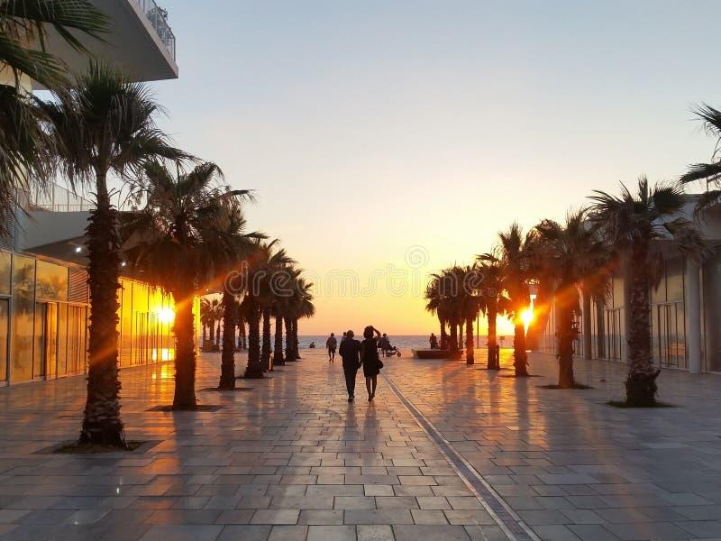 Una coppia che va guardare il tramonto sull'argine di Bat Yam, Israele immagine stock