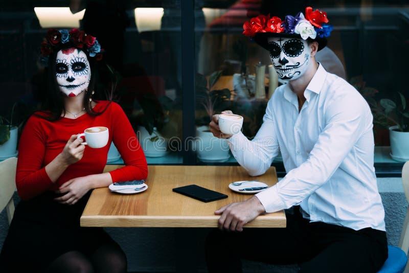Una coppia, cranio d'uso compensare Tutto il giorno di anima Trucco del cranio dello zucchero della ragazza e del ragazzo dipinto fotografia stock libera da diritti