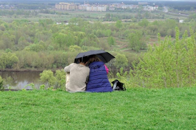 Una coppia del tipo e la ragazza stanno sedendo sull'erba verde sulla banca del fiume di Klyazma sotto un ombrello e sono fotografie stock