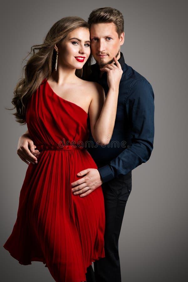 Una coppia di bellezza da moda, una bella donna in abiti rossi e un uomo elegante immagine stock