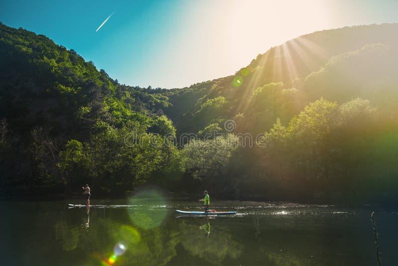 Una coppia di gente che galleggia lentamente sul fiume sul sup-bordo, contro le montagne ed il cielo blu immagini stock libere da diritti