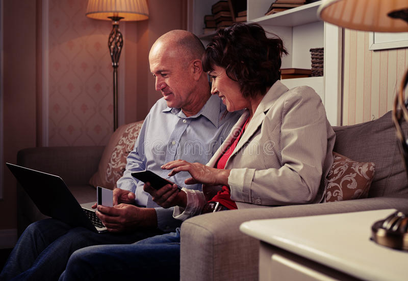 Una coppia di gente che guarda in un computer portatile immagine stock