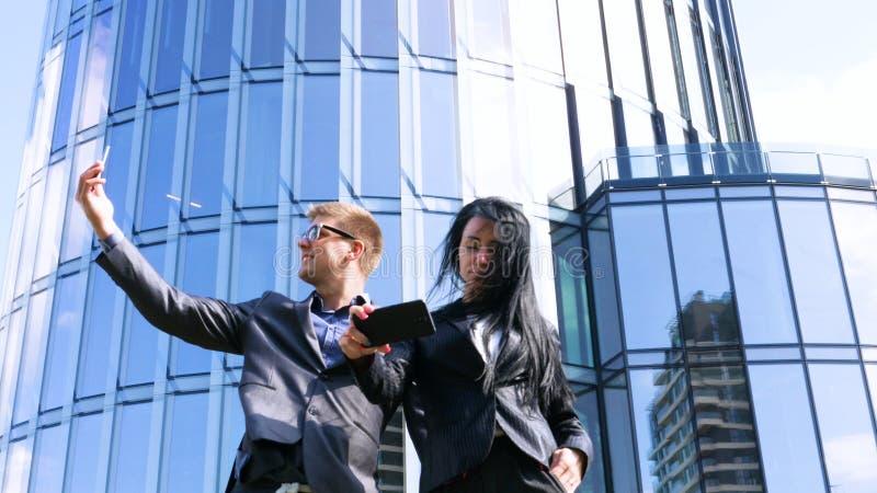 Una coppia di giovani divertenti in selfie con il cellulare sullo sfondo del grattacielo Concetto di: Suite, Business, Coppia, Ar immagini stock