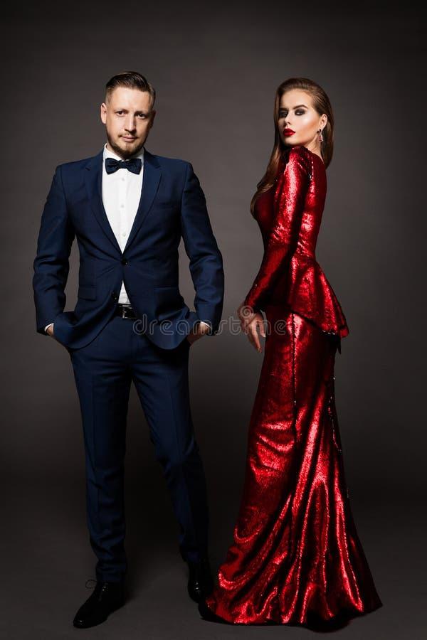 Una coppia di lusso, bellissima donna della moda in abiti rossi, elegante uomo in abito da sera immagini stock libere da diritti