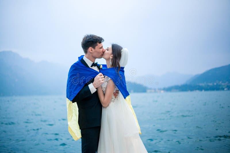 Una coppia di nozze che bacia sui precedenti di un lago e delle montagne fotografie stock