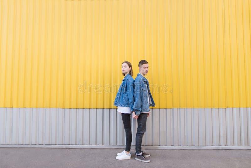Una coppia di pantaloni a vita bassa in rivestimenti del denim posano contro lo sfondo della parete fotografia stock