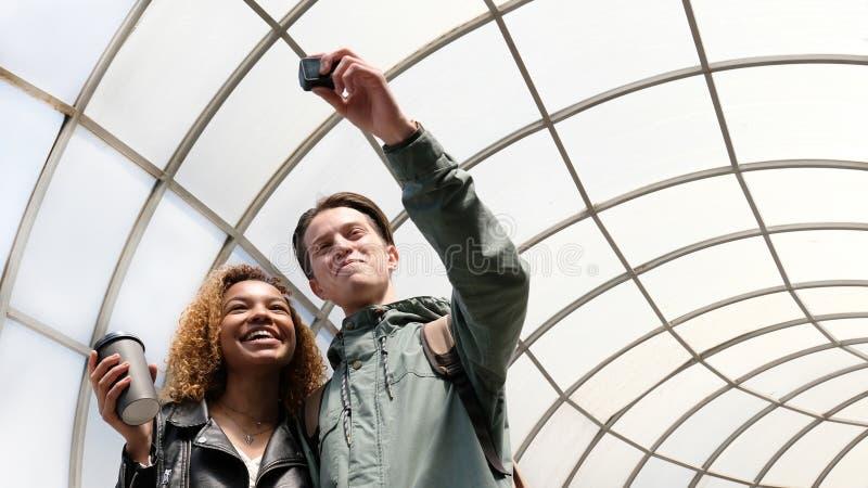 Una coppia di studenti con differenti colori della pelle fanno un video circa se stessi sulla macchina fotografica di azione Afro fotografia stock libera da diritti