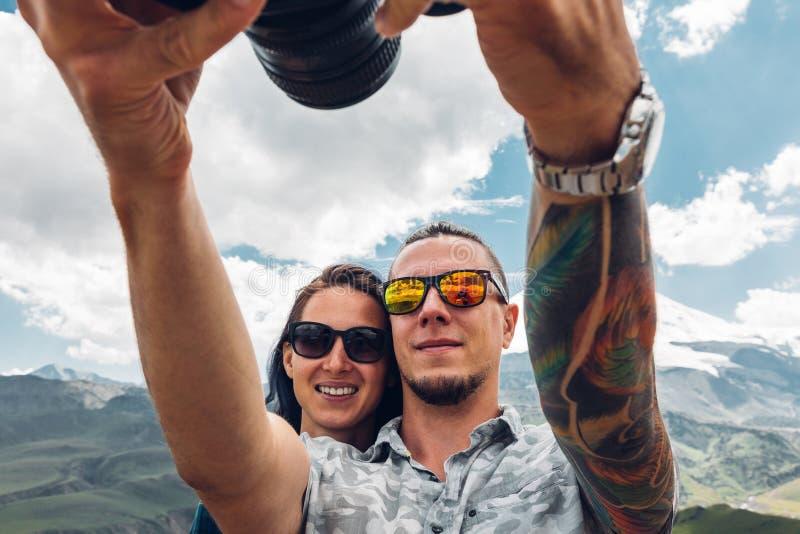 Una coppia di viaggiatori, un tipo e una ragazza, fanno il selfie su una macchina fotografica a fotografia stock