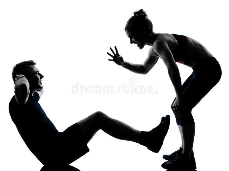 Una coppia equipaggia la donna che esercita la forma fisica di allenamento fotografia stock libera da diritti