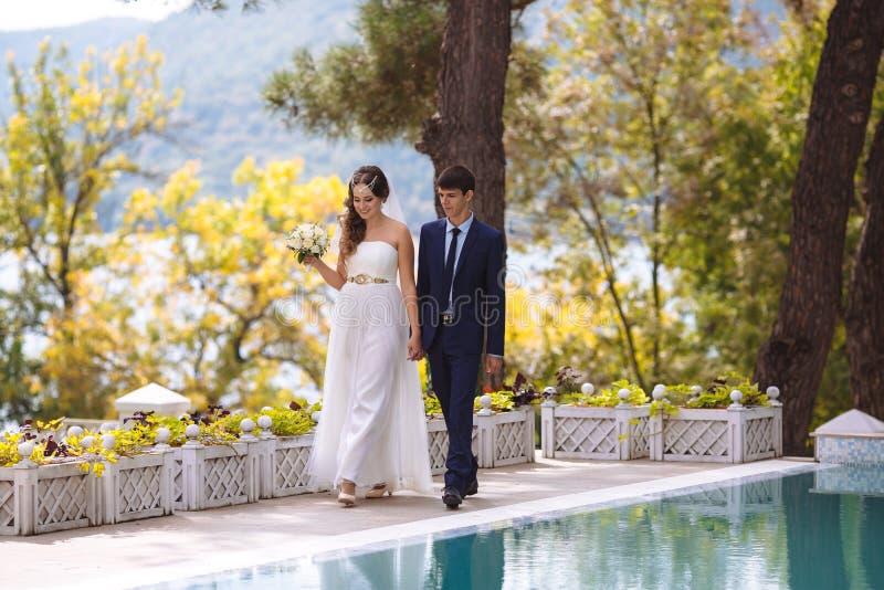 Una coppia felice ha sposato appena la marcia lungo il lungomare che si tiene per mano e che sorride allegramente Lle nozze attes immagini stock