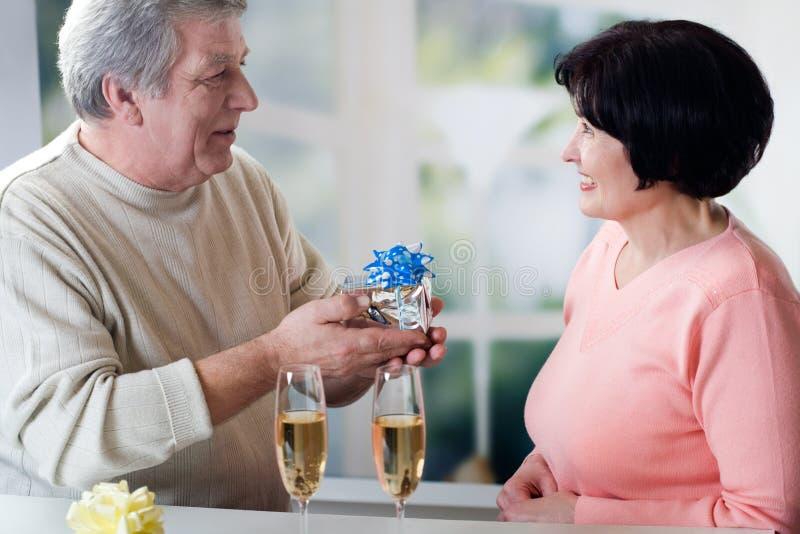 Una coppia matura felice che celebra i loro anni insieme al colore rosso immagine stock