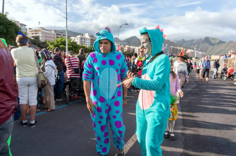 Una coppia nei supporti originali dei costumi del dinosauro e risate sulla via soleggiata durante il carnevale annuale sui fumett immagini stock
